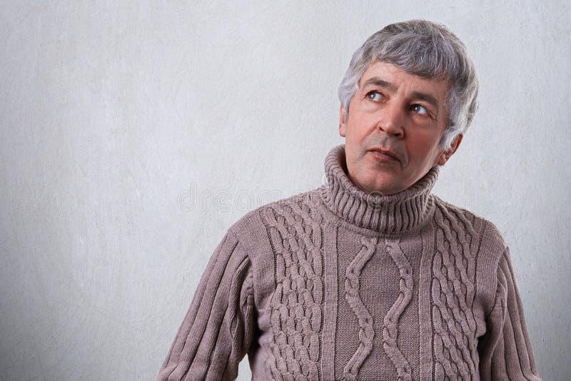 Een portret van aantrekkelijk bejaarde met rimpels die nadenkende en peinzende uitdrukking hebben die omhoog dragend sweater kijk royalty-vrije stock afbeeldingen