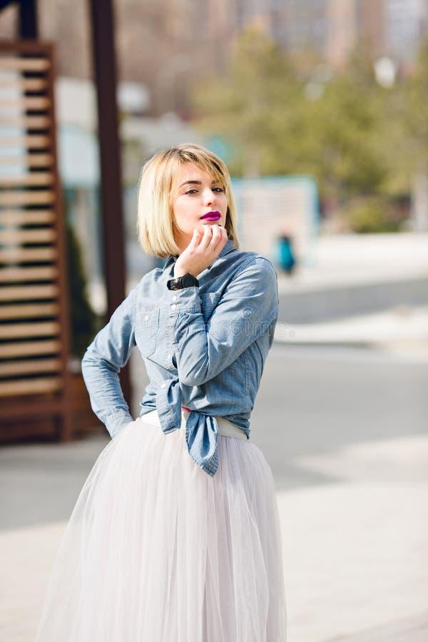 Een portret van een bevindend dromerig blondemeisje met heldere roze lippen die haar hand hoding dichtbij kin die grijs denimover stock foto