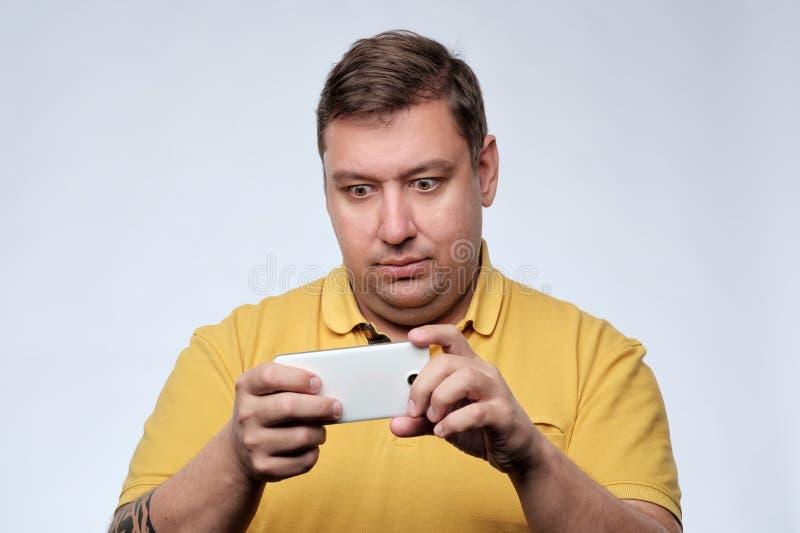 Een portret van de verraste jonge vette mens met mobiele telefoon royalty-vrije stock afbeeldingen