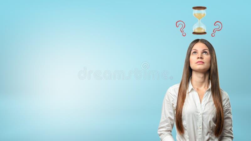 Een portret van een denkende onderneemster met een kleine zandloper en vraagtekens boven haar hoofd stock afbeelding