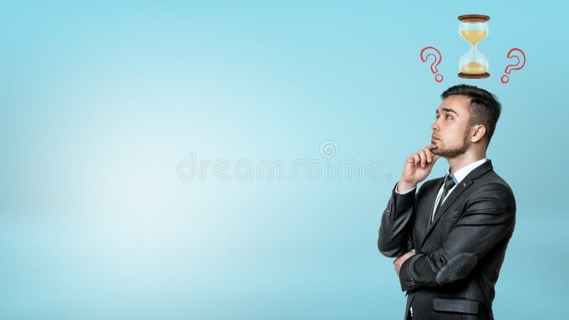 Een portret van een denkende zakenman met een kleine zandloper en vraagtekens boven zijn hoofd royalty-vrije stock fotografie