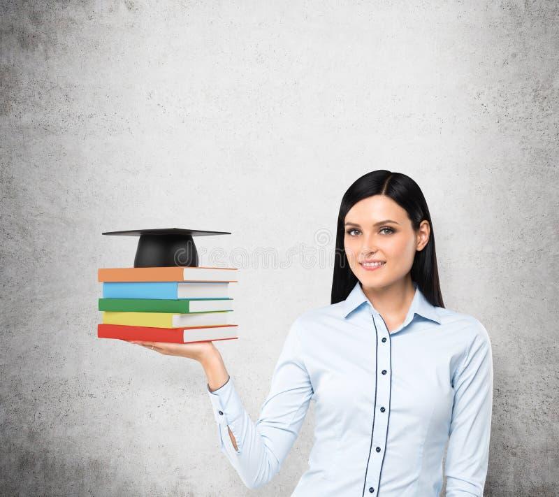 Een portret van een dame met de open palm die kleurrijke boeken en een graduatiehoed houdt Een concept noodzakelijk E-D stock foto's