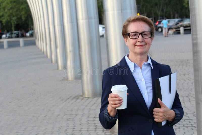 Een portret van een tevreden kijkende bedrijfsvrouw met holding om te gaan kop van koffie, documentenomslag en pen stock foto