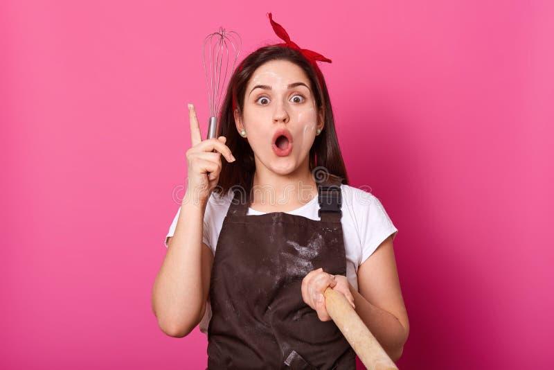 Een portret van enthousiaste energieke bakkersholding zwaait en deegrol in haar handen, kijkt creatief en de pret, stijgt haar, o royalty-vrije stock afbeelding