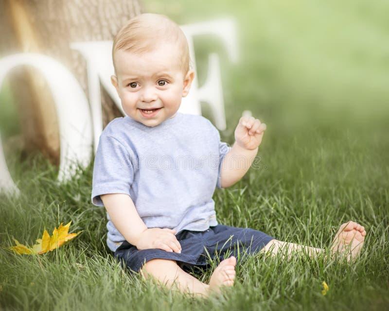 Een portret van een gelukkige leuke zitting van de babyjongen op groen gras openlucht bij de zomerdag Emoties, glimlach, grimas,  stock afbeeldingen