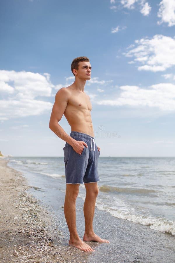 Een portret van gemiddelde lengte van een sexy jongen met een spiertorso bevindt zich op een kust op een natuurlijke vage achterg royalty-vrije stock fotografie
