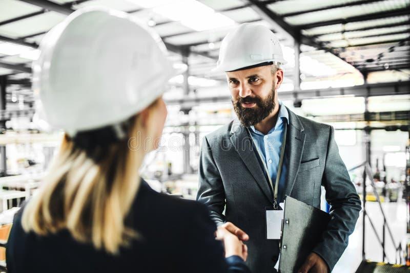 Een portret van een industriële man en vrouweningenieur in een fabriek, het schudden handen royalty-vrije stock foto