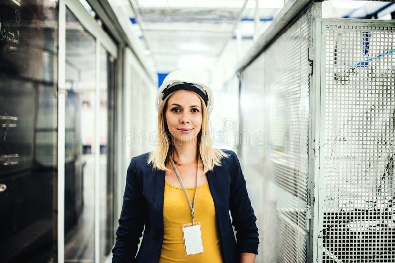 Een portret van een industriële vrouweningenieur die zich in een fabriek bevinden royalty-vrije stock fotografie