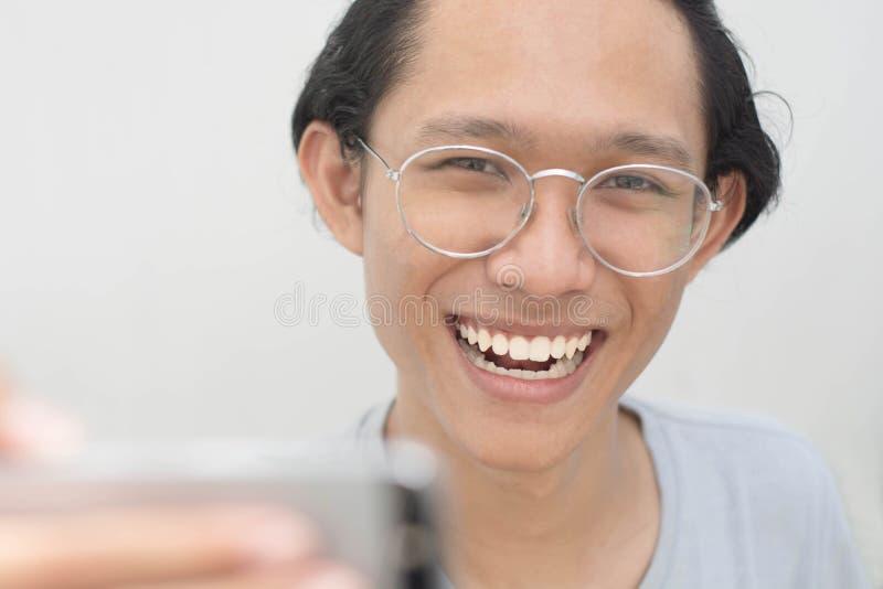 Een portret van een jonge aantrekkelijke mens die beelden van zelf hem nemen of selfie terwijl duim opgeeft stock afbeeldingen