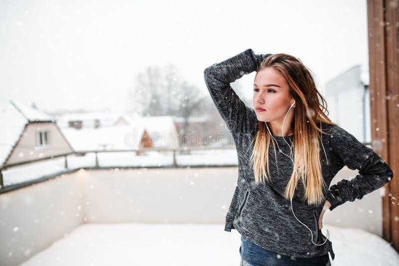 Een portret van jonge meisje of vrouw met oortelefoons in openlucht in de winter royalty-vrije stock fotografie