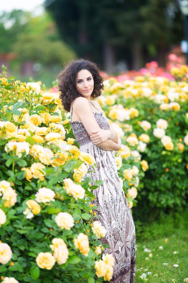 Een portret van Kaukasische jonge vrouw dichtbij gele rozen ringt in een roze tuin, kijkend recht aan de camera royalty-vrije stock fotografie
