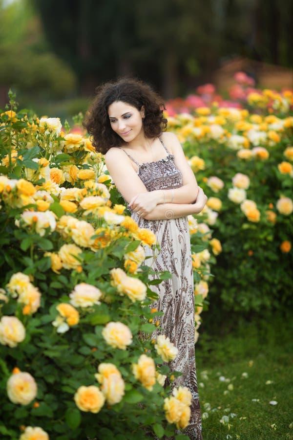 Een portret van Kaukasische jonge vrouw dichtbij gele rozen ringt in een roze tuin, kijkend recht aan de camera royalty-vrije stock afbeeldingen