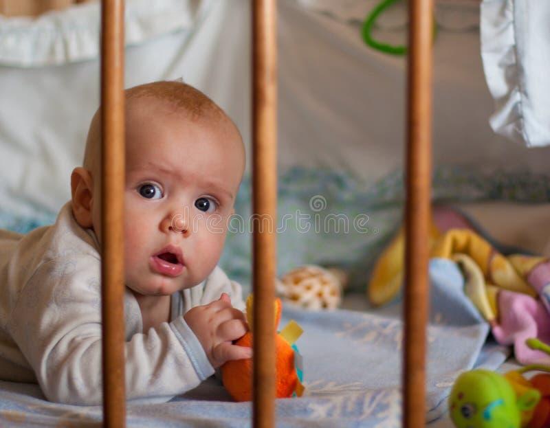 Een portret van een kleine jongen die in voederbak het spelen liggen royalty-vrije stock afbeelding