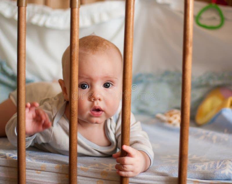 Een portret van een kleine jongen die in voederbak het spelen liggen royalty-vrije stock foto