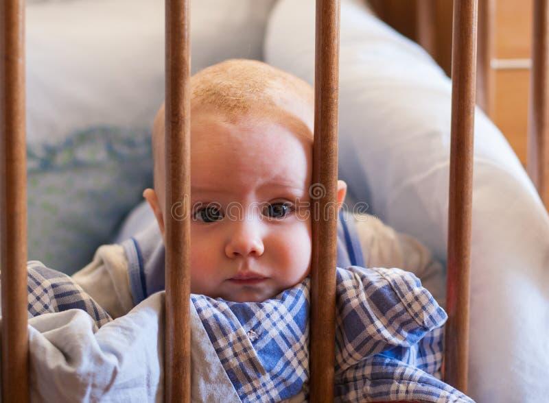 Een portret van een kleine jongen die in voederbak het spelen liggen stock foto