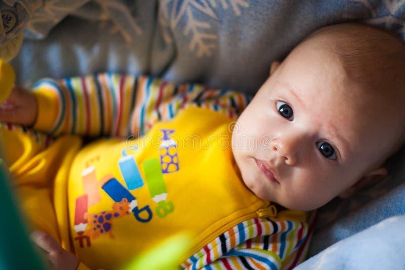 Een portret van een kleine jongen die in een voederbak liggen die ons bekijken stock foto's