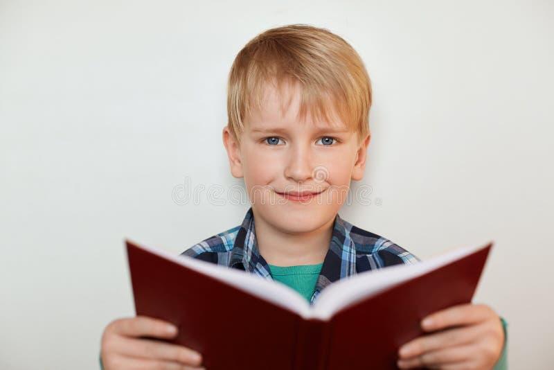 Een portret van knap weinig jongen die met eerlijk haar en blauwe ogen een boek in zijn handen houden terwijl status over witte a royalty-vrije stock foto's