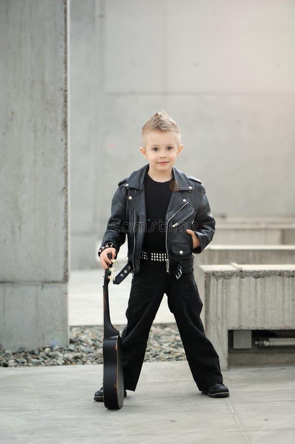 Een portret van knappe jongen in leerjasje en iroquois kapsel met gitaar royalty-vrije stock fotografie