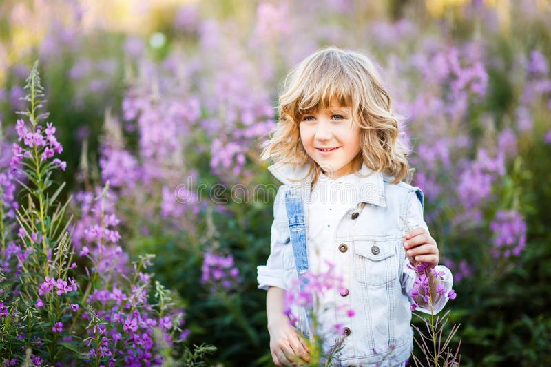Een portret van een leuke kleine jongen met blauwe ogen en lang blond haar buiten op het gebied van bloemen die pret hebben stock foto's