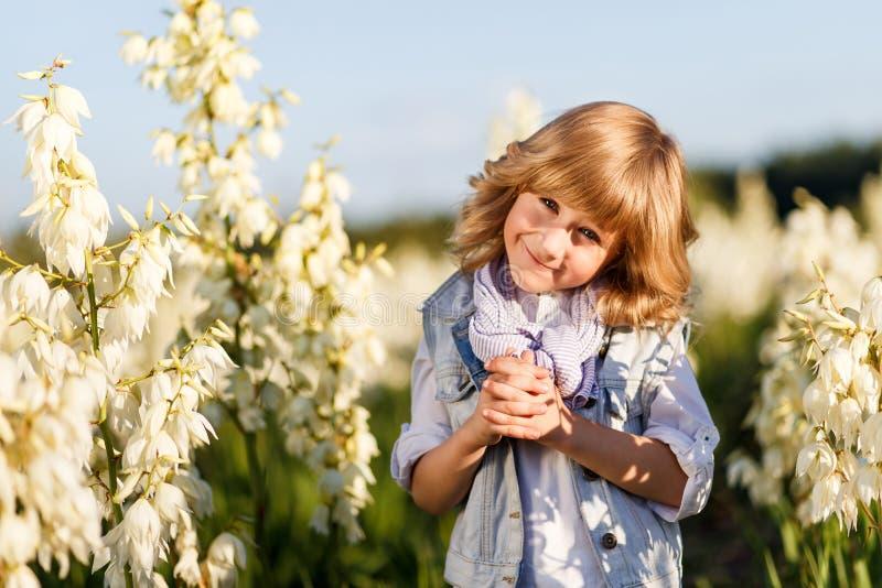Een portret van een leuke kleine jongen met blauwe ogen en lang blond haar buiten op het gebied van bloemen die pret hebben royalty-vrije stock afbeelding