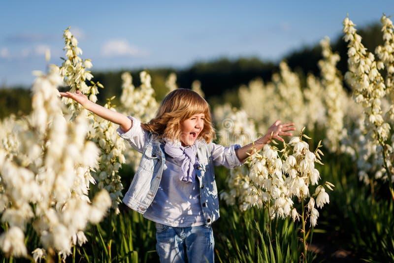 Een portret van een leuke kleine jongen met blauwe ogen en lang blond haar buiten op het gebied van bloemen die pret hebben stock fotografie