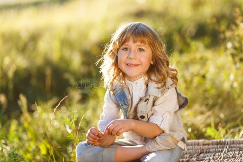 Een portret van een leuke kleine jongen met blauwe ogen en lange blonde haarzitting op een mand buiten bij zonsondergang stock afbeelding