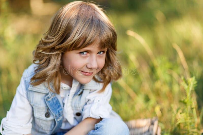 Een portret van een leuke kleine jongen met blauwe ogen en lange blonde haarzitting op een mand buiten bij zonsondergang royalty-vrije stock fotografie