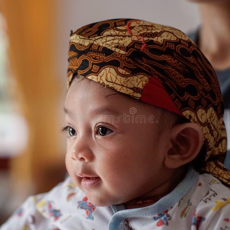 Een portret van een maand-oude baby 3 die een glimlach tonen en Blangkon dragen Blangkon is het typische hoofd behandelen van het stock foto