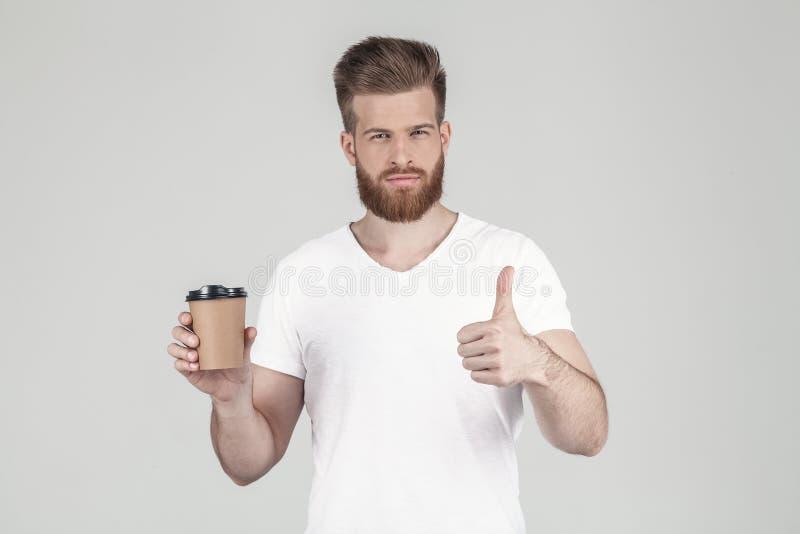 Een portret van een mooi geslacht hipster gekleed in een witte T-shirt houdt een kop van koffie in ??n hand en de andere shows stock foto