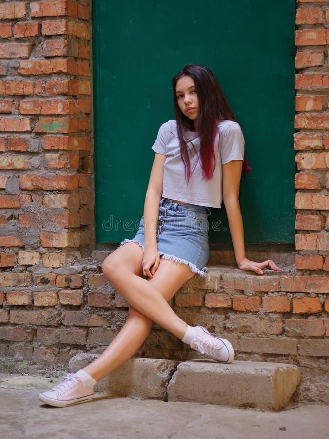 Een portret van een mooi meisje met donker haar in vrijetijdskleding die op een groene deurachtergrond stellen In stedelijk conce royalty-vrije stock fotografie