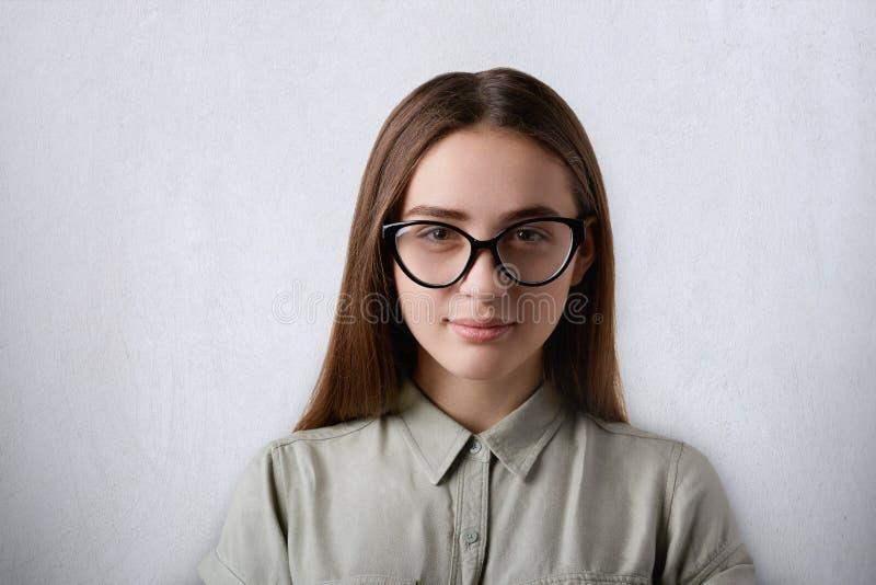 Een portret van mooi zeker meisje met lang recht haar die grote glassses dragen die wordt geïsoleerd camera bekijken die over gri royalty-vrije stock fotografie
