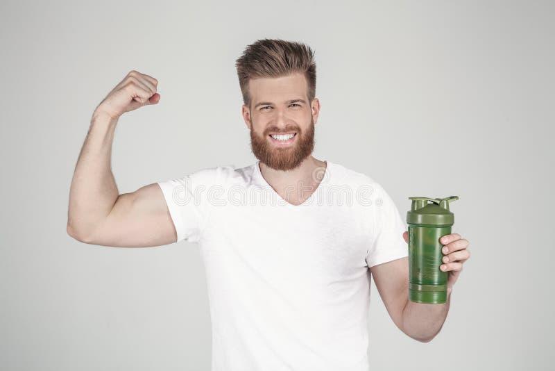 Een portret van een mooie mens met een baard en een modieus kapsel, gekleed in toevallige kleding, houdt een sportenschudbeker en stock afbeeldingen