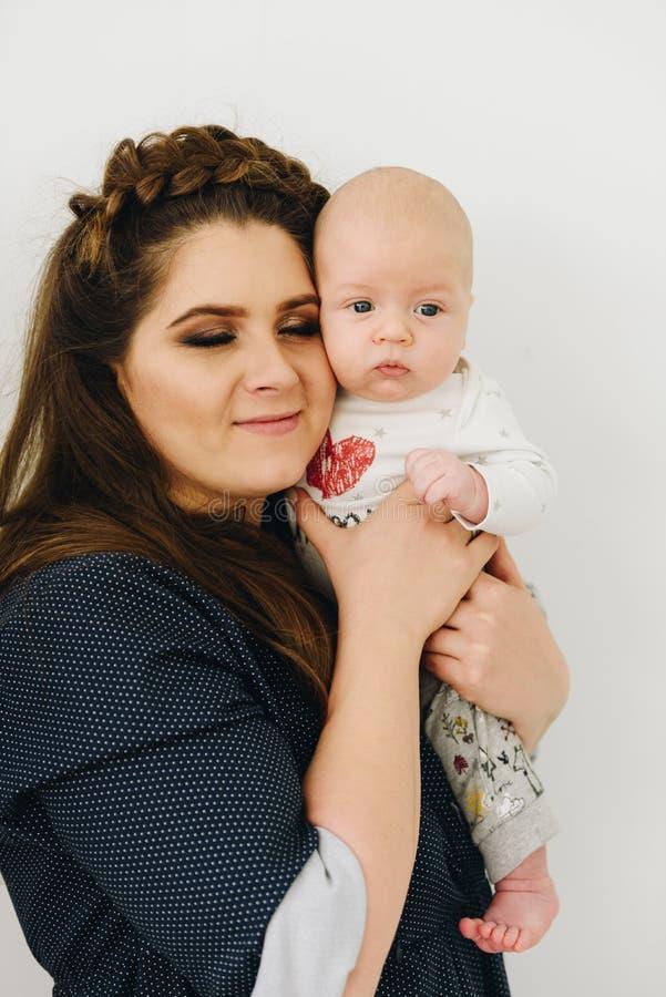 Een portret van ontspannen jonge mooie moeder die haar houden weinig baby stock fotografie