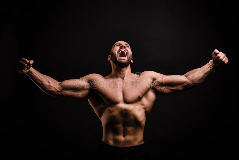 Een portret van een prachtige mens met naakt spiertorso op een verzadigde zwarte achtergrond sterk en machtsconcept stock fotografie