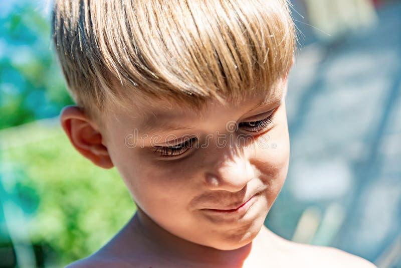 Een portret van een sluwe jongen die zijn neus rimpelde en over verraad dacht royalty-vrije stock afbeeldingen