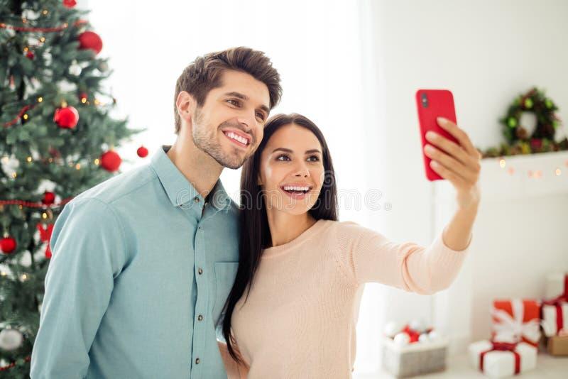 Een portret van twee mensen, een mooie man en een vrouw die zichzelf met hun mobiele telefoon maken, geniet van kersttijd thuis m royalty-vrije stock afbeeldingen