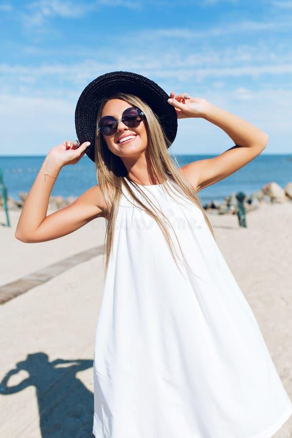 Een portret van vrij blond meisje met lang haar bevindt zich op het strand dichtbij overzees Zij draagt zwarte hoed, witte kledin royalty-vrije stock foto