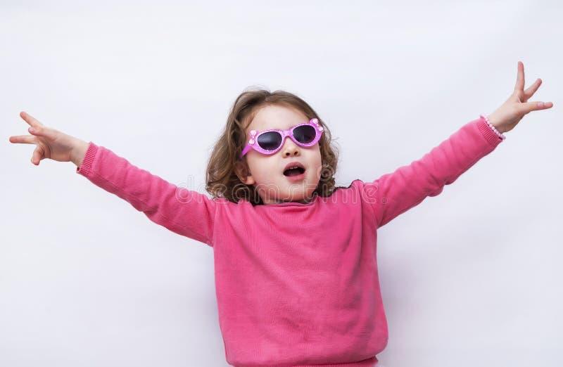 Een portret van een vrolijk meisje met glazen hief haar op indient de lucht royalty-vrije stock fotografie
