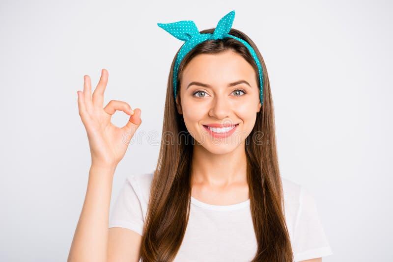 Een portret van een vrolijk, positief promotor meisje laat zien dat een goed teken uitstekende, perfecte advertenties aanbeveelt, stock afbeelding