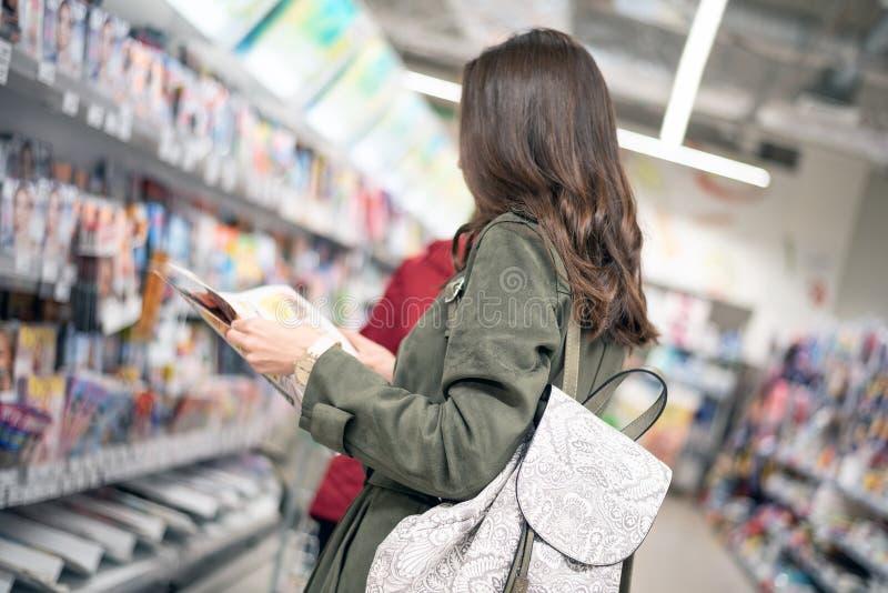 Een portret van een vrouw in de winkel bevindt zich voor het rek met tijdschriften en leest de productcatalogus royalty-vrije stock fotografie
