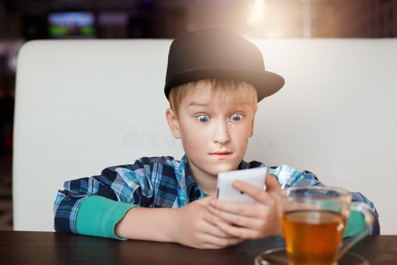 Een portret van weinig jongen modern overhemd dragen en GLB die bij koffie met een smartphone situeren die van de kop theeholding stock foto