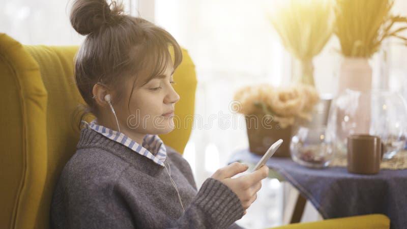 Een portretprofiel van een glimlachend meisje die in oortelefoons een telefoon houden stock afbeeldingen