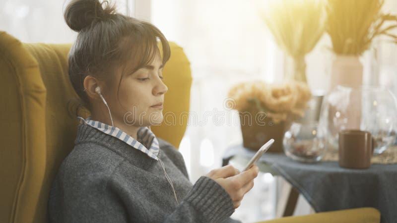 Een portretprofiel van een meisje die in oortelefoons een telefoon houden royalty-vrije stock afbeelding