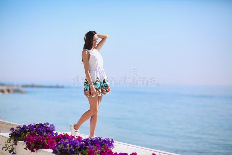 Een positief en gezond wijfje op een overzeese achtergrond Volledig-lengten van een mooi meisje die dichtbij een overzees strand  stock fotografie