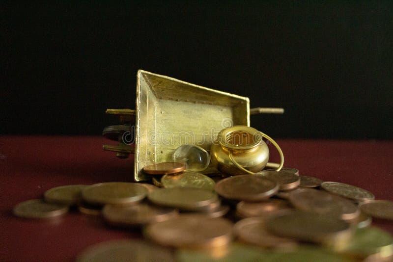 Een pot van goud en een kristalhalfedelsteen op partij van geldmuntstukken stock fotografie