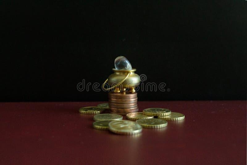 Een pot van goud en een kristalsteen bovenop een stapelmuntstukken stock afbeelding