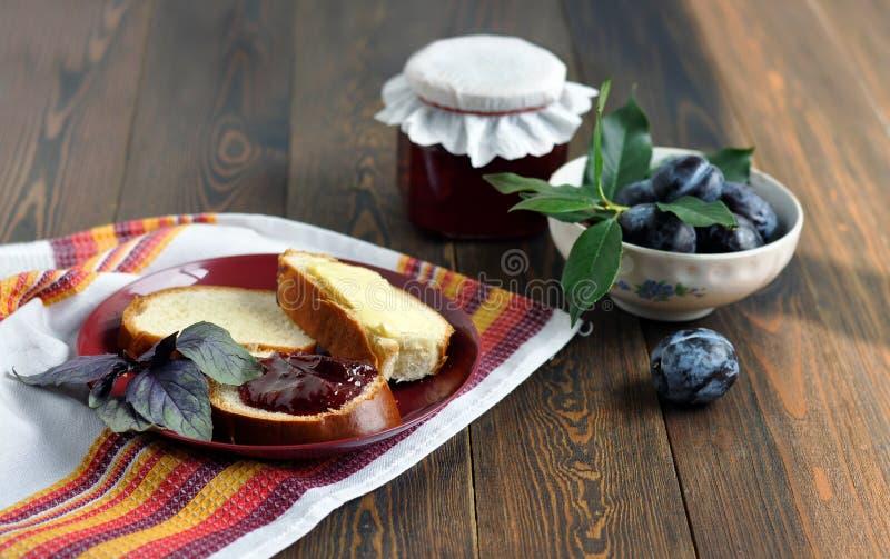 Een pot van zelfgemaakte vruchtenjam, rijpe pruimen, brood en boter op een rood bord. Donkerhouten tafel royalty-vrije stock fotografie
