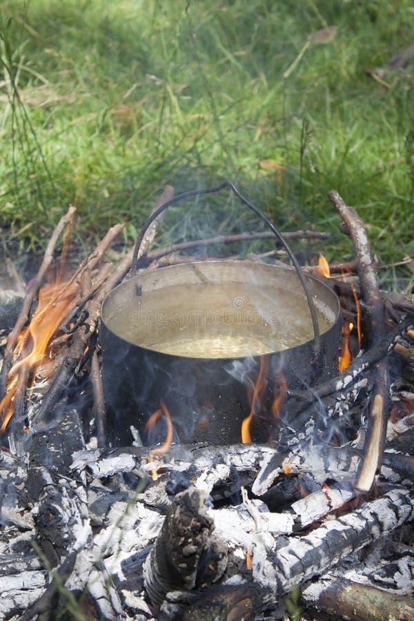 Een pot water wordt verwarmd op een brand gemaakt van takken royalty-vrije stock afbeelding