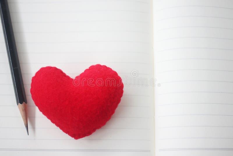 Een potlood en een rood hart worden geplaatst op een leeg boek royalty-vrije stock foto