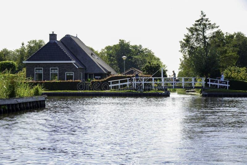 Een prachtig landschap tijdens de zomer met een kleine brug en fietstoeristen en met een typisch nederlands huis naast het kanaal stock afbeelding